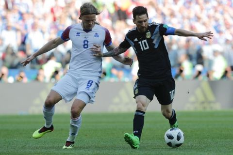 Argentina's Lionel Messi, right, challenges for the ball with Iceland's Birkir Bjarnason during the group D match between Argentina and Iceland at the 2018 soccer World Cup in the Spartak Stadium in Moscow, Russia, Saturday, June 16, 2018. (AP Photo/Ricardo Mazalan)