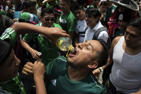 A fan has tequila poured down his throat during the celebration of Mexico's 2018 World Cup win over Germany at the Angel of Independence in Mexico City, Sunday, June 17, 2018. Mexico won it's first match against Germany 1-0. (AP Photo/Anthony Vazquez)