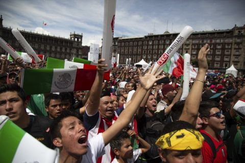 Fans celebrate Mexico's win during the Mexico vs. Germany World Cup soccer match, as they watched it on an outdoor screen in Mexico City's Zocalo, Sunday, June 17, 2018. Mexico won it's first match against Germany 1-0. (AP Photo/Anthony Vazquez)