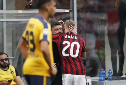 AC Milan's Ignazio Abate, right, celebrates with his coach Gennaro Gattuso after scoring his side's third goal during the Serie A soccer match between AC Milan and Hellas Verona at the San Siro stadium in Milan, Italy, Saturday, May 5, 2018. (AP Photo/Antonio Calanni)