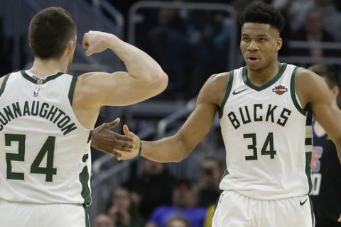 Milwaukee Bucks' Giannis Antetokounmpo (34) celebrates with Pat Connaughton (24) and Khris Middleton (22) during the first half of an NBA basketball game against the Los Angeles Clippers, Thursday, March 28, 2019, in Milwaukee. (AP Photo/Aaron Gash)