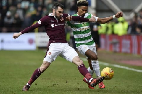 Hearts Michael Smith, left, tackles Celtic's Scott Sinclair during their Scottish Premiership soccer match at Tynecastle Stadium in Edinburgh, Scotland, Sunday Dec. 17, 2017.  Celtics record 69-match unbeaten run in Scottish soccer ended with a surprise thrashing on Sunday, when they lost 4-0 to Hearts, for their first defeat in any domestic competition since May 2016.(Ian Rutherford/PA via AP)