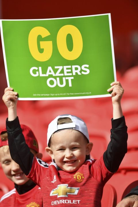 """A Manchester United fan holds a """"Go Glazers Out"""" banner inside the stadium before the English Premier League soccer match between Manchester United and Fulham at Old Trafford stadium in Manchester, England, Tuesday, May 18, 2021. (AP Photo/Paul Ellis, Pool)"""