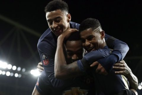 Manchester United's Anthony Martial, center, celebrates with teammates after scoring his side's third goal during the English FA Cup fourth round soccer match between Arsenal and Manchester United at the Emirates stadium in London, Friday, Jan. 25, 2019. (AP Photo/Matt Dunham)