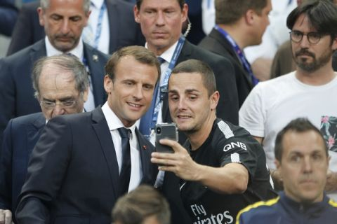 French President Emmanuel Macron, left, poses for a selfie with a soccer fan before the French Cup soccer final Paris Saint Germain against Les Herbiers at the Stade de France stadium in Saint-Denis, outside Paris, Tuesday, May 8, 2018. (AP Photo/Francois Mori)