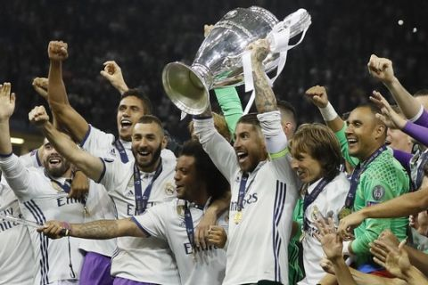 Real Madrid captain Sergio Ramos raises the trophy after the Champions League final soccer match between Juventus and Real Madrid at the Millennium stadium in Cardiff, Wales Saturday June 3, 2017. (AP Photo/Kirsty Wigglesworth)