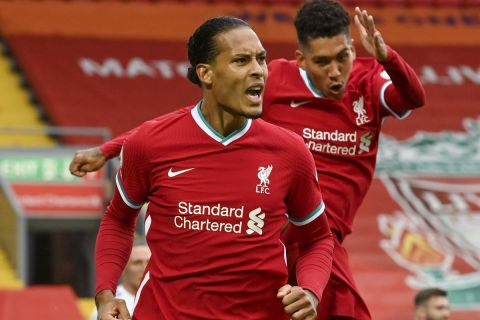 Liverpool's Virgil van Dijk, left, celebrates with Liverpool's Roberto Firmino after he scored his side's second goal during the English Premier League soccer match between Liverpool and Leeds United, at the Anfield stadium, in Liverpool, Saturday, Sept. 12, 2020. (Paul Ellis, Pool via AP)