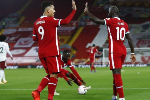 Liverpool's Sadio Mane, right, is congratulated by teammate Roberto Firmino after scoring his team's first goal during the English Premier League soccer match between Liverpool and Arsenal at Anfield in Liverpool, England, Monday, Sept. 28, 2020. (Jason Cairnduff/Pool via AP)