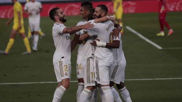 Real Madrid's Karim Benzema, right, celebrates with his teammates after scoring during the Spanish La Liga soccer match between Real Madrid and Villareal at the Alfredo di Stefano stadium in Madrid, Spain, Thursday, July 16, 2020. (AP Photo/Bernat Armangue)