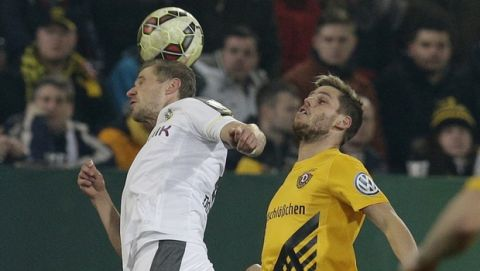 Dortmund's Oliver Kirch, left, and Dresden's Justin Eilers go for a header during the German soccer cup round of sixteen match between third division team Dynamo Dresden and first division team Borussia Dortmund in Dresden, Germany, Tuesday, March 3, 2015. (AP Photo/Michael Sohn)