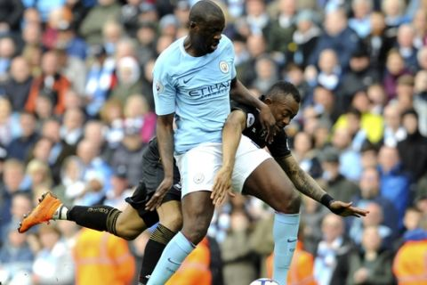 Manchester City's Yaya Toure, left, and Swansea's Jordan Ayew battle for the ball during the English Premier League soccer match between Manchester City and Swansea City at Etihad stadium in Manchester, England, Sunday, April 22, 2018. (AP Photo/Rui Vieira)