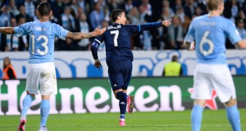 Real Madrid's Portuguese forward Cristiano Ronaldo (C) celebrates after scoring the opening goal during the UEFA Champions League first-leg Group A football match between Malmo FF and Real Madrid CF at the Swedbank Stadion, in Malmo, Sweden on September 30, 2015. .AFP PHOTO / JONATHAN NACKSTRAND        (Photo credit should read JONATHAN NACKSTRAND/AFP/Getty Images)