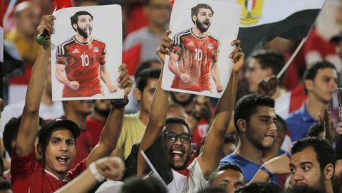 Soccer fans hold poster of Egyptian national soccer team player and Liverpool's star striker Mohammed Salah during Egypt's final practice for the World Cup soccer tournament at Cairo Stadium in Cairo, Egypt, Saturday, June 9, 2018. Thousands of fans gathered at Cairo's main stadium Saturday to watch Egypt's last home practice before flying to Grozny, Chechnya, where they'll set up base during their World Cup campaign in Russia. (AP Photo/Amr Nabil)