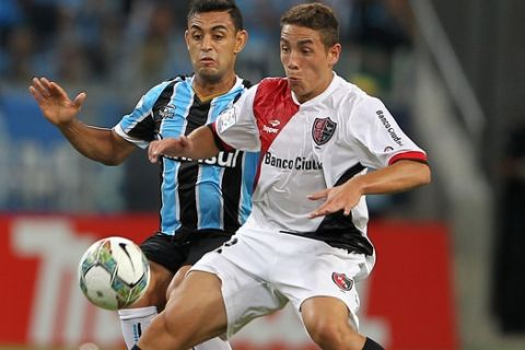 Ezequiel Ponce of Argentina's Newell's Old Boys, right, fights for the ball with Werley of Brazil's Gremio during their Copa Libertadores soccer match in Porto Alegre, Brazil, Thursday, March 13, 2014. (AP Photo/Nabor Goulart)