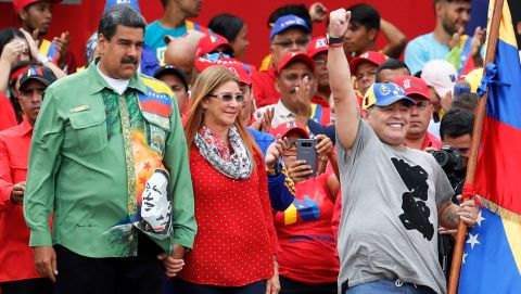 Venezuela's President Nicolas Maduro, left, holds hands with his his wife, first lady Cilia Flores, as they stand with Argentina's former soccer player Diego Maradona on stage during Maduro's closing reelection campaign rally in Caracas, Venezuela, Thursday, May 17, 2018. Maduro is seeking a new six-year mandate on May 20, and despite crippling hyperinflation and widespread shortages of food and medicine, is widely expected to win a contest that opponents denounce as a fraud and have been condemned by much of the international community. (AP Photo/Ariana Cubillos)