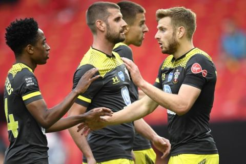 Southampton's Stuart Armstrong, right, is congratulated by teammate Kyle Walker-Peters after scoring his teams first goal during the English Premier League soccer match between Manchester United and Southampton at Old Trafford in Manchester, England, Monday, July 13, 2020. (AP Photo/Peter Powell,Pool)