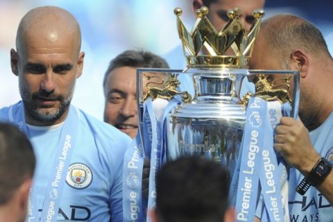 Manchester City manager Josep Guardiola, left, looks at the English Premier League trophy after the soccer match between Manchester City and Huddersfield Town at Etihad stadium in Manchester, England, Sunday, May 6, 2018. (AP Photo/Rui Vieira)