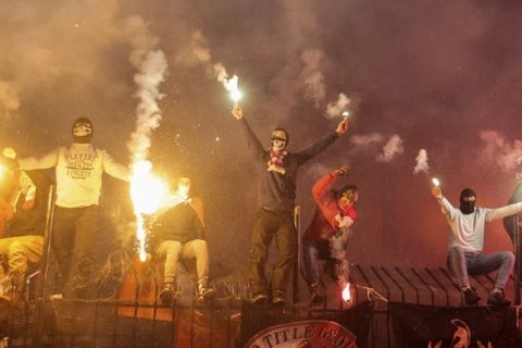 """FILE - In this photo taken on Friday, Dec. 1, 2017, Russian soccer fans of Spartak team burn flares during a Russian Premier League Championship soccer match between Arsenal Tula and Spartak Moscow in Tula, about 200 kilometers (125 miles) south of Moscow, Friday, Dec. 1, 2017. So-called """"ultras"""" focus on coordinated chants, lighting flares and staging elaborate displays at games, but can defend themselves if needed. The hardcore fighters mostly stick to pre-arranged brawls in forests because of tight stadium surveillance. Some fighters are drifting away from football and turning to organized mixed martial arts events which offer a chance to make money from their hobby. (AP Photo/Denis Tyrin, file)."""