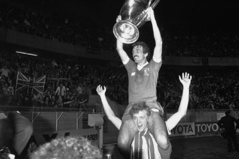 Liverpool player Alan Kennedy, who scored the only goal in the match, sits on the shoulders of team-mate Phil Neal, while holding the European Football Cup trophy, after they had defeated Real Madrid in the Final at the Parc Des Princes, Paris on May 27, 1981. Liverpool defeated Real 1-0. (AP Photo/Staff/Lipchitz)