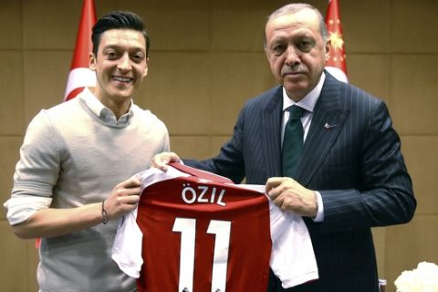 """In this photo taken on Sunday, May 13, 2018, Turkey's President Recep Tayyip Erdogan, right, poses for a photo with Turkish-German Arsenal soccer player Mesut Ozil in London. Erdogan started a three-day visit to Britain on Sunday by praising the country as """"an ally and a strategic partner, but also a real friend."""" (Presidential Press Service/Pool via AP)"""