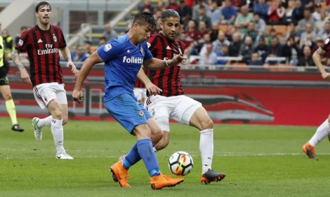 Fiorentina's Giovanni Simeone, left, scores his side's opening goal as AC Milan's Ricardo Rodriguez tries to stop him during the Serie A soccer match between AC Milan and Fiorentina at the San Siro stadium in Milan, Italy, Sunday, May 20, 2018. (AP Photo/Antonio Calanni)