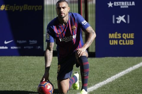 FC Barcelona new signing Kevin-Prince Boateng kneels on the pitch during his presentation at the Camp Nou stadium in Barcelona, Spain, Tuesday, Jan. 22, 2019. Barcelona surprisingly signed Kevin-Prince Boateng on loan from Italian club Sassuolo on Monday until the end of the season. The 31-year-old Boateng has appeared to be past his prime after playing for the likes of AC Milan, Borussia Dortmund, Schalke, and Tottenham. (AP Photo/Emilio Morenatti)
