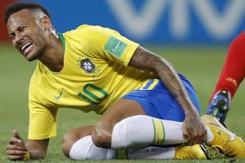 Brazil's Neymar holds his shinbone during the quarterfinal match between Brazil and Belgium at the 2018 soccer World Cup in the Kazan Arena, in Kazan, Russia, Friday, July 6, 2018. (AP Photo/Francisco Seco)