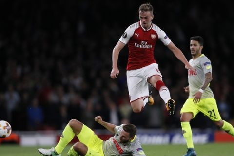Cologne's Marco Hoeger, bottom, and Arsenal's Rob Holding challenge for the ball during the Europa League group H soccer match between Arsenal and FC Cologne at the Emirates stadium in London, England, Thursday, Sept. 14, 2017 . (AP Photo/Kirsty Wigglesworth)