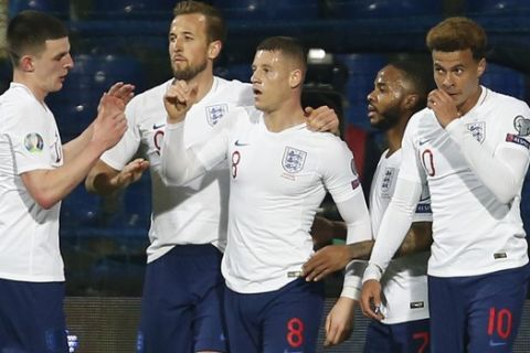 England players celebrate with teammate Ross Barkley, center, who scored his side's second goal during the Euro 2020 group A qualifying soccer match between Montenegro and England at the City Stadium in Podgorica, Montenegro, Monday, March 25, 2019. (AP Photo/Darko Vojinovic)