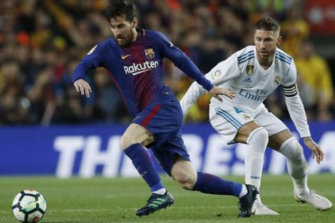 Barcelona's Lionel Messi, left, steers the ball past Real Madrid's Sergio Ramos during a Spanish La Liga soccer match between Barcelona and Real Madrid, dubbed 'el clasico', at the Camp Nou stadium in Barcelona, Spain, Sunday, May 6, 2018. (AP Photo/Manu Fernandez)