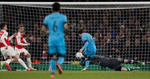 Barcelona's Argentinian forward Lionel Messi (2R) scores his team's first goal during the UEFA Champions League round of 16 1st leg football match between Arsenal and Barcelona at the Emirates Stadium in London on February 23, 2016. . / AFP / ADRIAN DENNIS        (Photo credit should read ADRIAN DENNIS/AFP/Getty Images)