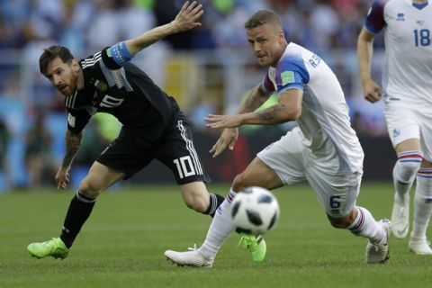 Argentina's Lionel Messi, left, and Iceland's Ragnar Sigurdsson challenge for the ball during the group D match between Argentina and Iceland at the 2018 soccer World Cup in the Spartak Stadium in Moscow, Russia, Saturday, June 16, 2018. (AP Photo/Matthias Schrader)