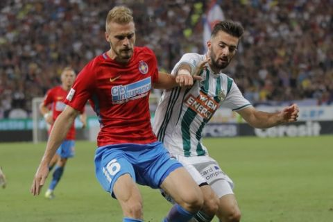 Steaua's Bogdan Planic challenges for the ball with Rapid's Marvin Potzmann during the Europa League playoffs, second leg, soccer match between FCSB Steaua Bucharest and Rapid Vienna at the National Arena in Bucharest, Romania, Thursday, Aug. 30, 2018. (AP Photo/Vadim Ghirda)