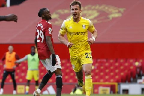 Fulham's Joe Bryan celebrates after scoring his side's opening goal during the English Premier League soccer match between Manchester United and Fulham at Old Trafford stadium in Manchester, England, Tuesday, May 18, 2021. (AP Photo/Phil Noble, Pool)
