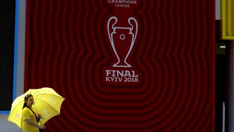 A woman holds an umbrella as she stands next to a giant banner of the Champions League soccer final, at a fan-zone in Kiev, Ukraine, Thursday, May 24, 2018. Liverpool will play Real Madrid in the Champions League Final on May 26 at the Olympiyski stadium in Kiev. (AP Photo/Sergei Grits)