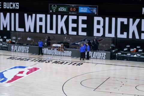 Officials stand beside an empty court before the scheduled start of an NBA basketball first round playoff game between the Milwaukee Bucks and the Orlando Magic, Wednesday, Aug. 26, 2020, in Lake Buena Vista, Fla. (AP Photo/Ashley Landis, Pool)
