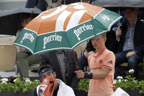 Argentina's Juan Martin Del Potro sits under an umbrella as he plays Croatia's Marin Cilic during their quarterfinal match of the French Open tennis tournament at the Roland Garros stadium, Wednesday, June 6, 2018 in Paris. Play is being delayed by rain during the French Open men's quarterfinals. (AP Photo/Alessandra Tarantino)