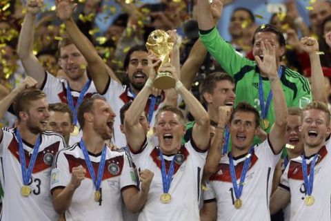 FILE - In this July 13, 2014 file photo Germany's Bastian Schweinsteiger holds up the World Cup trophy as the team celebrates their 1-0 victor over Argentina after the World Cup final soccer match between Germany and Argentina at the Maracana Stadium in Rio de Janeiro, Brazil. Germany captain Bastian Schweinsteiger said Friday, July 29, 2016 he is quitting the national team. The 31-year-old said in a Twitter statement that hes asked Germany coach not to include him in the line-up in future.  (AP Photo/Natacha Pisarenko, file)