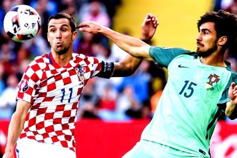 Croatia's Darijo Srna, left, challenges Portugal's Andre Gomes during the Euro 2016 round of 16 soccer match between Croatia and Portugal at the Bollaert stadium in Lens, France, Saturday, June 25, 2016. (AP Photo/Geert Vanden Wijngaert)