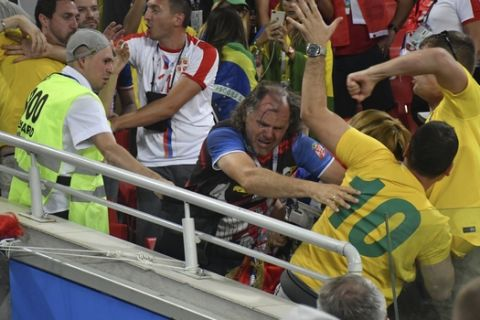 Serbia and Brazilia soccer fans fight each other during the group E match between Serbia and Brazil, at the 2018 soccer World Cup in the Spartak Stadium in Moscow, Russia, Wednesday, June 27, 2018. (AP Photo)