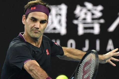 FILE - In this Thursday, Jan. 30, 2020 file photo, Switzerland's Roger Federer makes a backhand return to Serbia's Novak Djokovic during their semifinal match at the Australian Open tennis championship in Melbourne, Australia. Roger Federer offered stuck-at-home amateurs the ultimate online fantasy camp, a chance to get tennis tips from a GOAT. While people all over the world are cooped up because of the new coronavirus -- social distancing while trying to stay healthy and help others do the same -- a bunch of athletes have been posting workouts and drills on social media with suggestions for staying in shape. Federer did that sort of thing, too, on Tuesday, April 7, 2020. (AP Photo/Andy Brownbill, File)