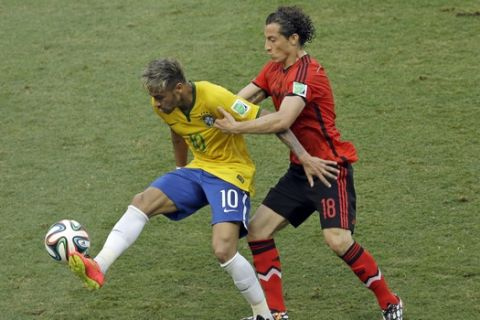 Mexico's Andres Guardado, right, holds Brazil's Neymar during the group A World Cup soccer match between Brazil and Mexico at the Arena Castelao in Fortaleza, Brazil, Tuesday, June 17, 2014.  (AP Photo/Themba Hadebe)