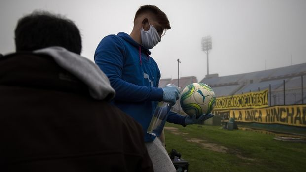 A ball catcher wearing plastic gloves and a face mask amid the new coronavirus pandemic, disinfects the ball during a local championship soccer match between Nacional and Penarol in Montevideo, Uruguay, Sunday, Aug. 9, 2020. (AP Photo/Matilde Campodonico)