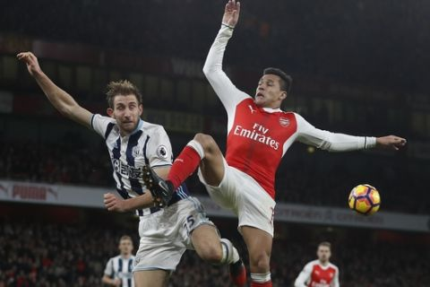 Arsenal's Alexis Sanchez, right, vies for the ball with West Brom's Craig Dawson during the English Premier League soccer match between Arsenal and West Bromwich Albion at Emirates stadium in London, Monday, Dec. 26, 2016. (AP Photo/Kirsty Wigglesworth)