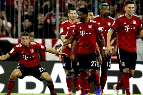 Bayern's Thomas Mueller, left, celebrates after scoring his side's opening goal during the German Bundesliga soccer match between FC Bayern Munich and TSG 1899 Hoffenheim in Munich, Germany, Friday, Aug. 24, 2018. (AP Photo/Matthias Schrader)