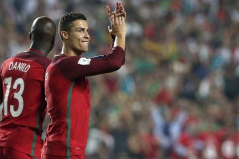 Portugal's Cristiano Ronaldo, right, and Danilo celebrate at the end of the World Cup Group B qualifying soccer match between Portugal and Switzerland at the Luz stadium in Lisbon, Tuesday, Oct. 10, 2017. (AP Photo/Armando Franca)