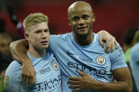 Manchester City's Vincent Kompany, right and Manchester City's Kevin De Bruyne celebrate after winning the English League Cup defeating Arsenal 3-0 in the final at Wembley stadium in London, Sunday, Feb. 25, 2018.(AP Photo/Tim Ireland)