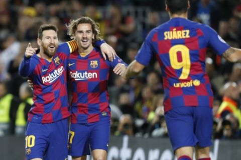 Barcelona's Lionel Messi, left, celebrates after scoring his side's second goal with Antoine Griezmann, centre and Luis Suarez during a Champions League soccer match Group F between Barcelona and Dortmund at the Camp Nou stadium in Barcelona, Spain, Wednesday, Nov. 27, 2019. (AP Photo/Joan Monfort)