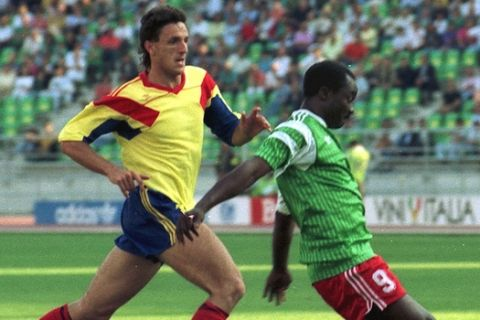 FILE - The June 14, 1990 file photo shows Cameroon's Roger Milla, right, being] about to score the first of his two goals against Romania, as Romanian defender Gheorghe Popescu tries to stop him, during the World Cup soccer match in Bari, Italy. This was to be Africa's World Cup, not just the first to take place on the continent but also a chance for its teams to excel. Mostly, however, it's been another letdown, and the post-mortems have begun.  Explanations abound _ and several have the ring of truth: weak youth development programs, lack of depth on the national teams, overreliance on non-African coaches hired for brief World Cup tenures, national governing bodies that lack world-class professionalism. The bottom line: Africa's six World Cup teams _ the most ever in the tournament _ produced flashes of brilliance and feistiness,  but collectively failed to close the gap with Europe and South America.    (AP Photo/Giulio Broglio)