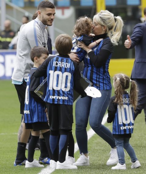 Inter Milan's Mauro Icardi is surrounded by his sons and wife Wanda Nara after receiving a prize for his100 goals with the Inter Milan jersey, prior to the start of a Serie A soccer match between Inter Milan and Hellas Verona, at the San Siro stadium in Milan, Italy, Saturday, March 31, 2018. (AP Photo/Luca Bruno)